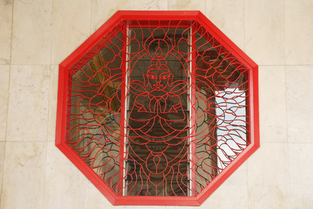 lattice window: Octagonal window with lattice work showing Buddha LANG_EVOIMAGES