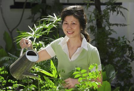 regando plantas: Una mujer regar las plantas en el jardín LANG_EVOIMAGES