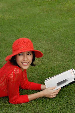 A woman reads while lying on grass