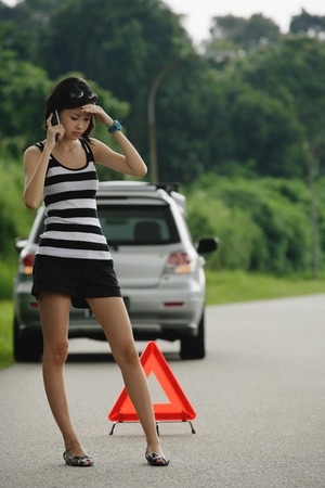 A woman with car trouble calls for help on her cellphone