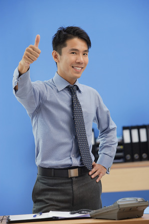 professionally: Businessman giving thumbs up at camera