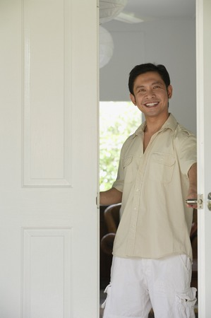 homeownership: Man at home, standing at doorway, smiling