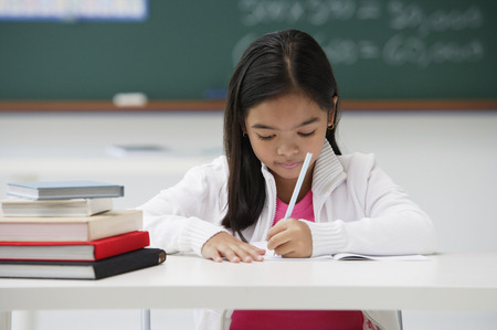 Girl writing and sitting at school desk