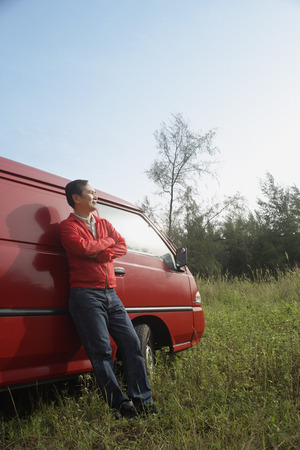 leaning against: Man leaning against red van, outdoors in nature
