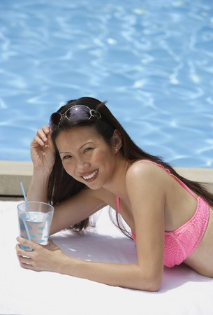 homeownership: Woman in pink bikini, lying by swimming pool, holding a glass of water, smiling at camera
