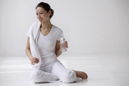 Woman sitting on floor with towel and water bottle, relaxing