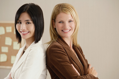 noteboard: Two female colleagues smile at the camera together