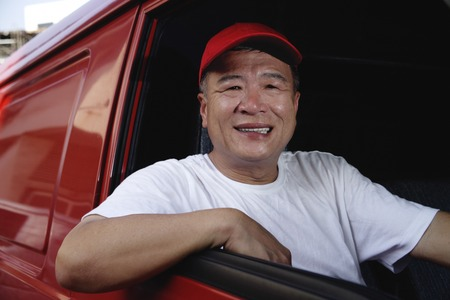 only 1 person: A man in a red van smiles at the camera LANG_EVOIMAGES