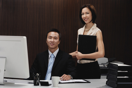 A man and a woman smile at the camera while they are at work