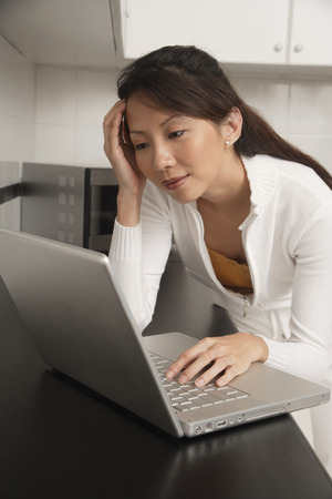 affluence: Woman in kitchen leaning on counter staring at laptop  computer, with head resting on hand