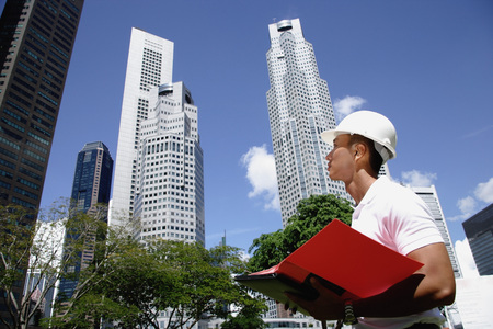 professionally: A man with a helmet stands in front of skyscrapers LANG_EVOIMAGES