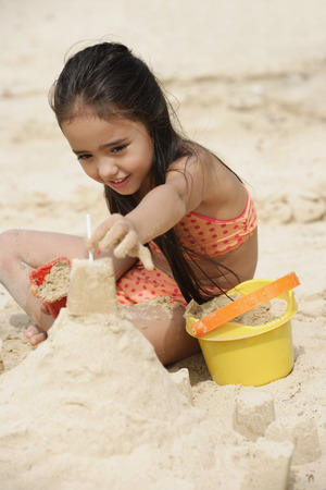 Young girl building sand castle on beach Stock Photo