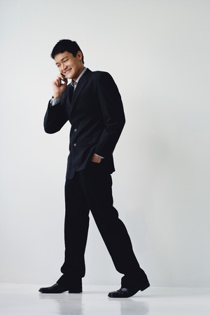 A man in a suit smiles as he talks on his cellphone