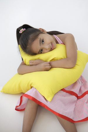 only 1 person: A young girl hugs a cushion