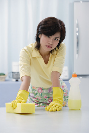 Woman in kitchen wearing gloves, cleaning kitchen counter with sponge LANG_EVOIMAGES