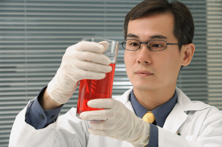 Scientist examining container of fluid Stock Photo