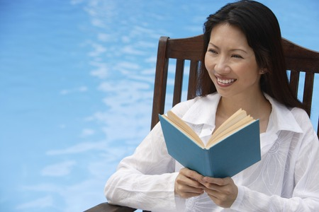 homeownership: Woman by swimming pool, reading a book, looking away