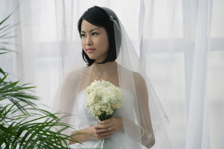 fulfil: A bride holds a bouquet of flowers LANG_EVOIMAGES