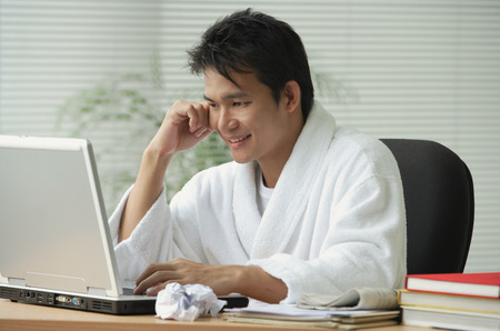 Man in bathrobe working at computer