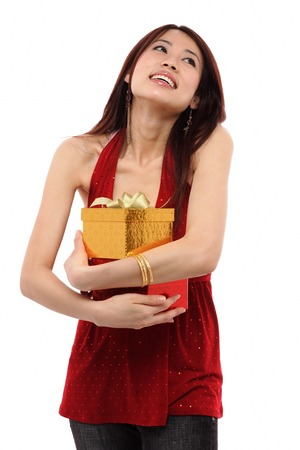 hair wrapped up: Young woman holding two presents, looking up LANG_EVOIMAGES