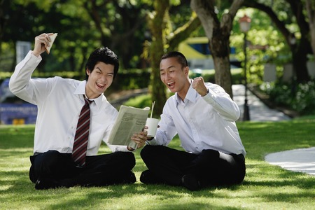 Two men get excited as they read the newspaper in the park