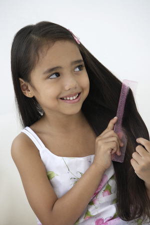 multi age: A young girl combs her hair