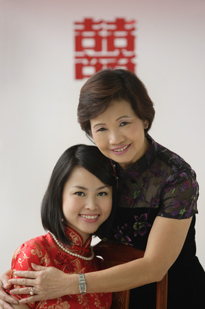wedding customs: A bride and her mother hug and smile at the camera