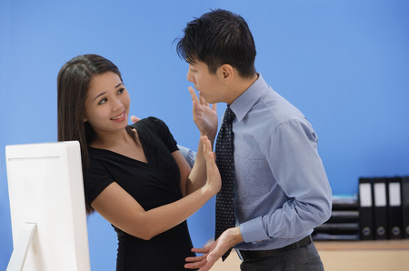 Woman pushing away businessman