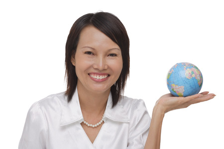 Woman holding globe and smiling at camera