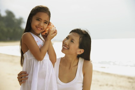 Mother and daughter on beach, daughter with conk shell to ear listening to ocean
