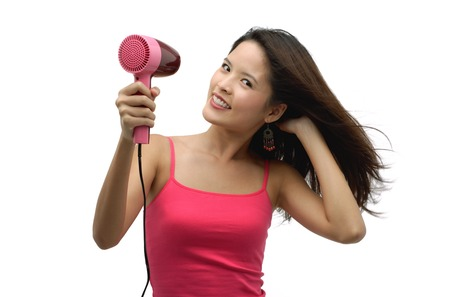 Young woman blow drying hair and looking at camera Stock Photo