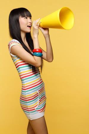 Joven mujer gritando a través del megáfono amarillo