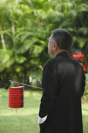 only 1 person: Man in traditional clothing, standing in park holding Chinese lantern