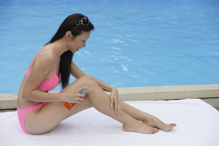 homeownership: Woman in pink bikini, sitting by swimming pool, applying sun tan lotion on her legs