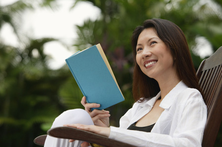 homeownership: Woman sitting outdoors, reading a book, looking away