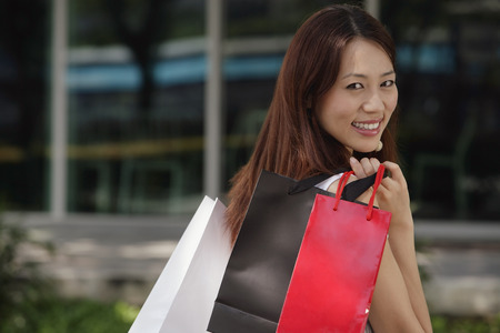 over the shoulder: Woman with shopping bags, smiling over shoulder at camera LANG_EVOIMAGES