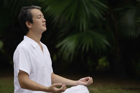 homeownership: Mature man sitting outdoors, meditating
