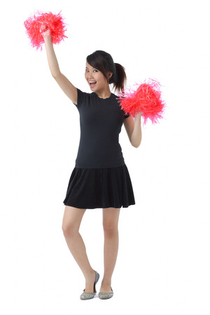 Young woman cheerleading with pom poms