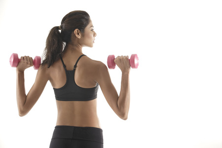 Woman with back to camera, lifting weights, working out