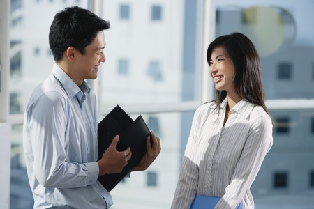 Two colleagues smile as they talk to each other