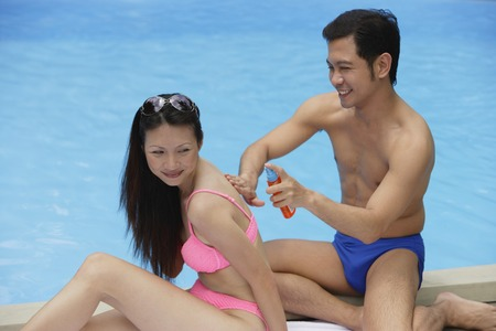 homeownership: Couple by swimming pool, man applying sun tan lotion on woman