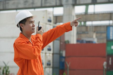 only 1 person: Construction worker giving directions on walkie talkie LANG_EVOIMAGES