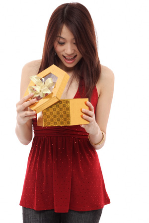 hair wrapped up: Young woman opening present and looking inside box LANG_EVOIMAGES