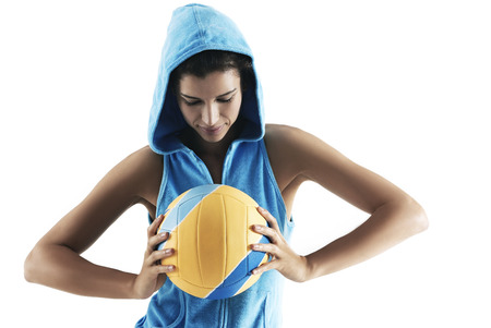 Woman holding volley ball, looking at ball, wearing hood, sports Stock Photo