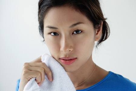 A young woman looks at the camera as she washes her face LANG_EVOIMAGES