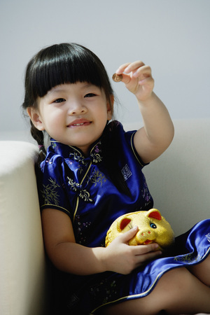 only 1 person: A small girl in blue silk cheongsam plays with a piggy bank LANG_EVOIMAGES