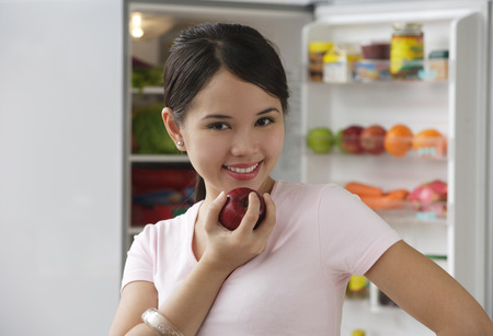 Young woman holding apple and smiling at camera Stock Photo