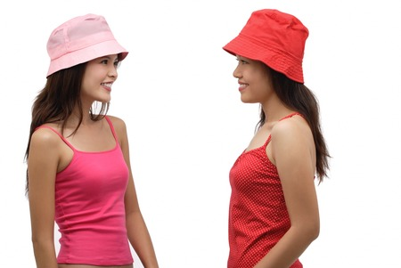 Two young women wearing pink and red hats, looking at each other