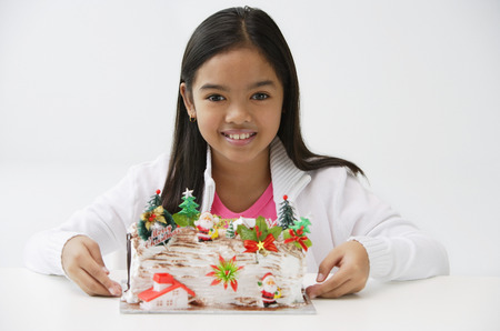 Girl with Christmas log cake smiling at camera