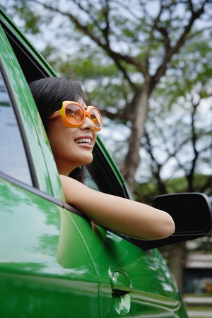 A young woman drives a green car Imagens